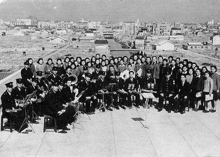 The employees' chorus of Osaka Gas pose on the roof of the Shinmachi police station with the damaged city in the background.